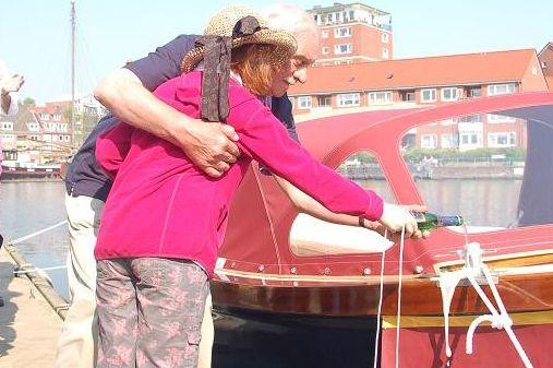 Zu sehen ist eine ältere Dame, welcher auf das Boot Falderndelft geholfen wird