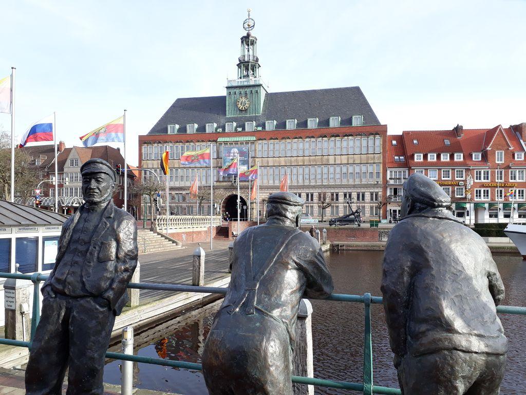Man sieht Hinni den Delftspucker und seine beiden Freunde Jan und Joke. Drei Bronzefiguren, welche oberhalb des Ratsdelftes stehen. Im Hintergrund das ostfriesische Landesmuseum