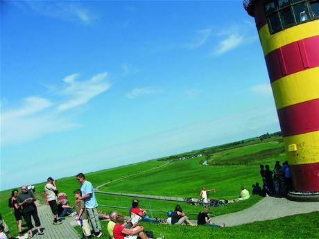 Zu sehen ist ein Teil des Pilsumer Leuchtturms mit seiner charakteristischen rot-gelben Farbe. Die Sonne scheint und einige Menschen befinden sich auf dem Deich vor dem Leuchtturm