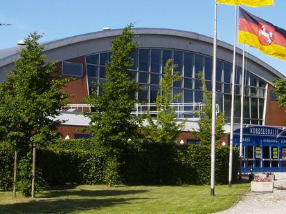 Zu sehen ist die Nordseehalle von Außen mit Büschen und Bäumen und einer Flagge