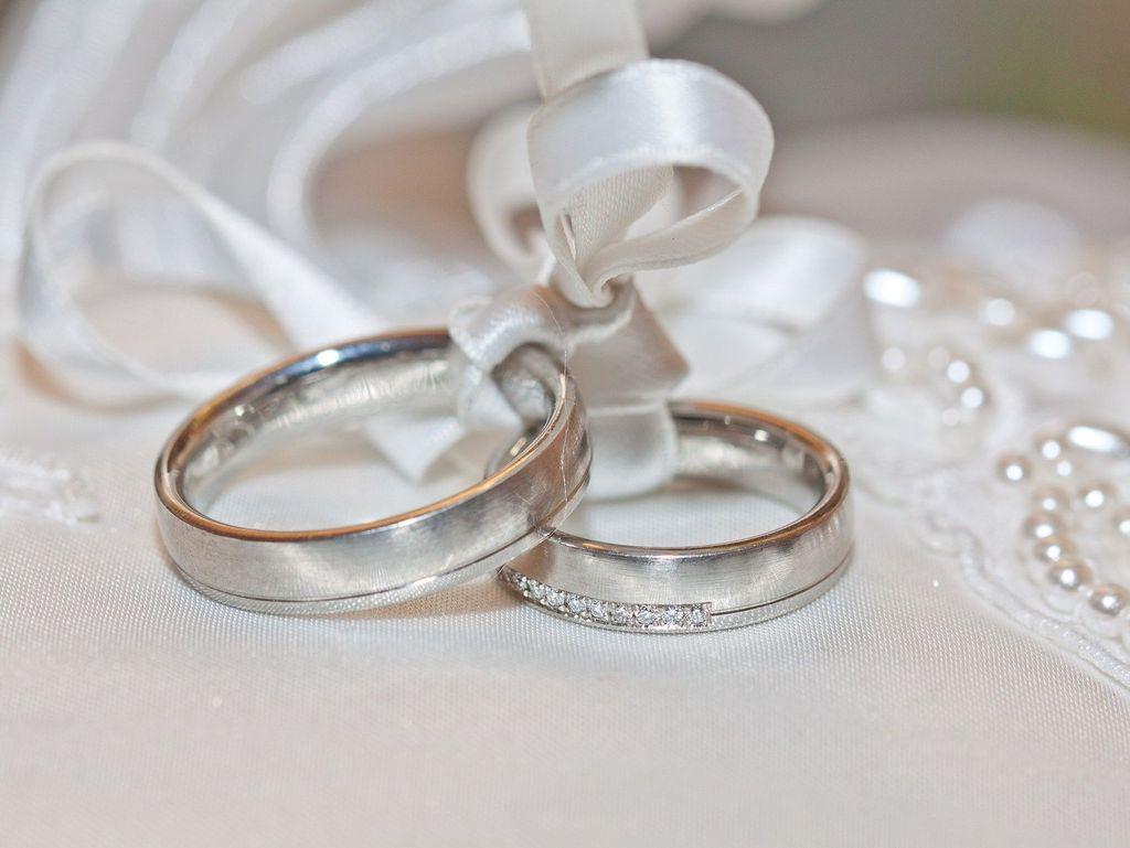 Zu sehen sind 2 Eheringe auf einem weißen Ringkissen als Nahaufnahme