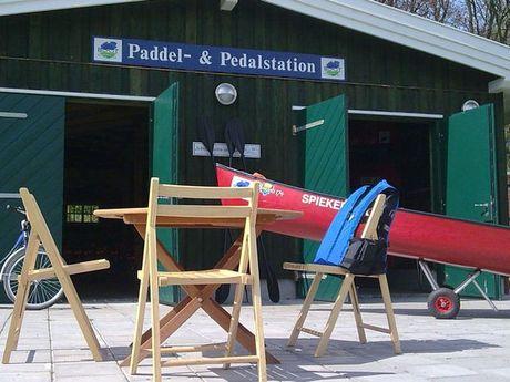 Zu sehen ist das Häuschen der Paddel und Pedalstation in Emden im Hintergrund. Im Vordergrund sind Stühle, ein Kanu und ein Fahrrad zu sehen