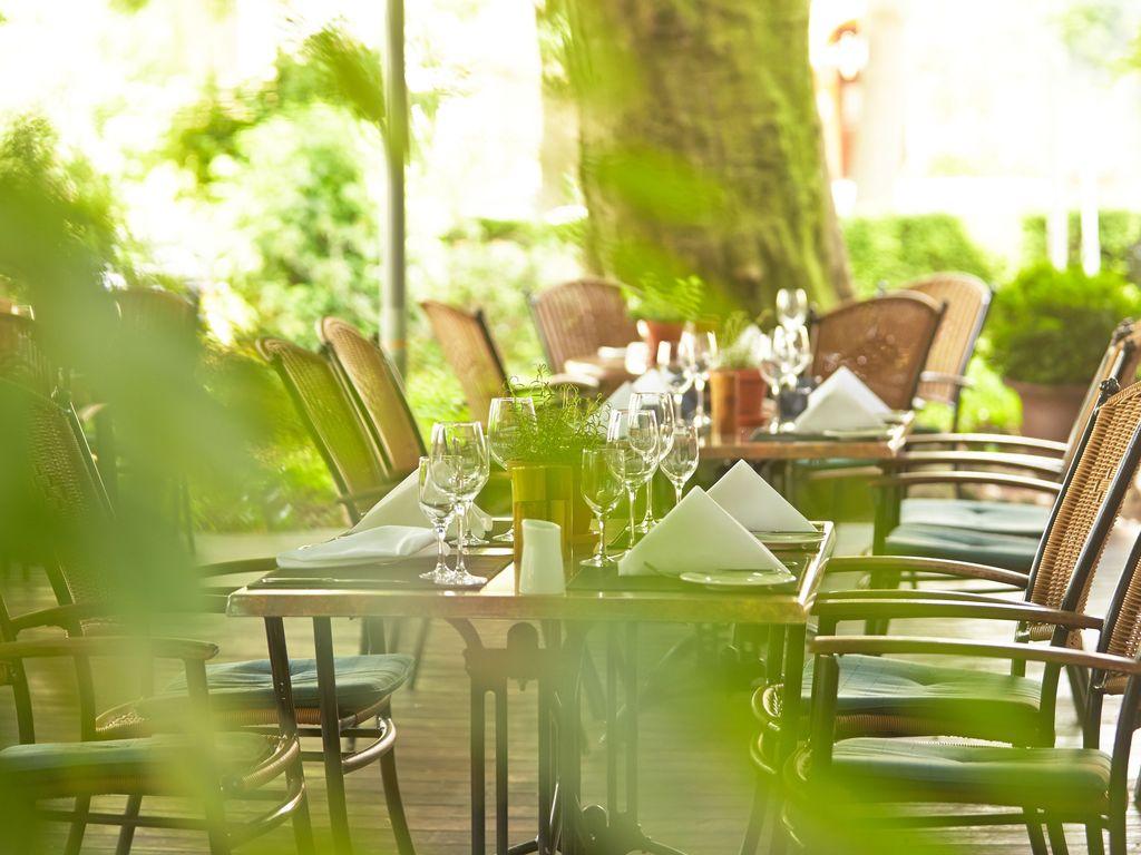 Zu sehen sind Tische und Stühle im Außenbereich, im Vordergrund kann man leicht verschwommen Grünpflanzen erahnen