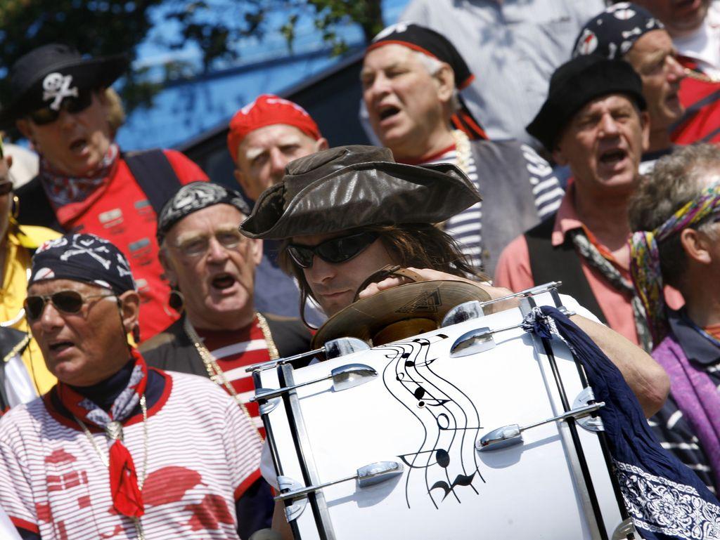 Als Piraten verkleidete Musikgruppe. Im Mittelpunkt ein junger Mann mit großer Trommel