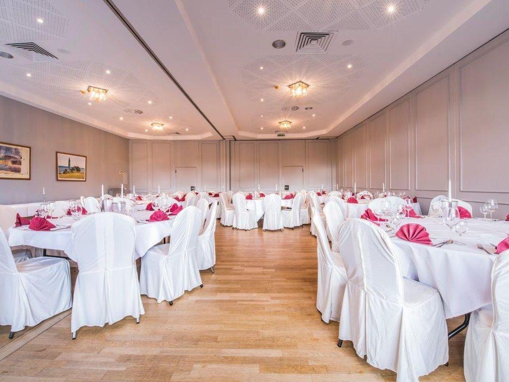 Zu sehen ist ein hell ausgeleuchteter Saal mit festlich wirkenden Tischen und Stühlen