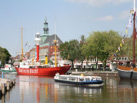 Blick vom Hafentorplatz auf den Ratsdelft. Das gerade auslaufende Hafenboot hat das Feuerschiff passiert, im Hintergrund sieht man teile des Ostfriesischen Landesmuseums