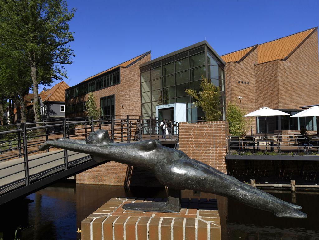 Im Vordergrund ist eine Statue in einer liegenden Position zu sehen. Dahinter die Brücke welche zur Kunsthalle führt und die Kunsthalle selber.