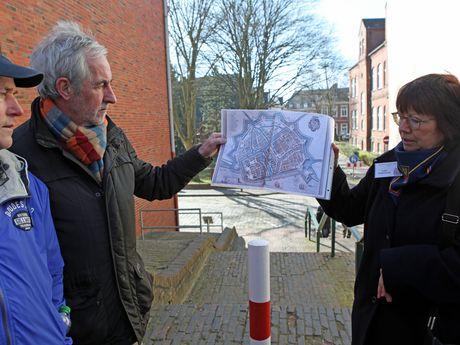 Eine Stadtführerin steht mit weiteren Personen an der alten Emsmauertreppe. Sie hält einen historischen Stadtplan in der Hand und erzählt, wie es dort früher aussah