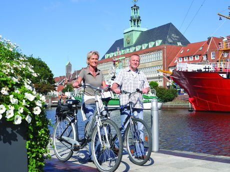 Ein Paar geht mit Fahrrädern an einem Blumenkübel am Delft entlang. Im Hintergrund sieht man das Ostfriesische Landesmuseum und ein Teil des Feuerschiffes