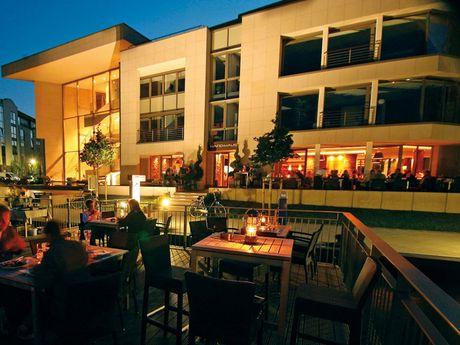 Zu sehen ist das Restaurant Hafenhaus von der Wasser-Terrasse aus fotografiert in der blauen Stunde, mit Beleuchtung.