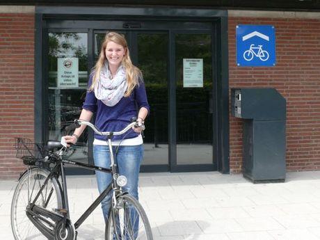 Zu sehen ist der Eingang der Fahrradgarage am Bahnhof. Davor eine junge Frau mit ihrem Fahrrad