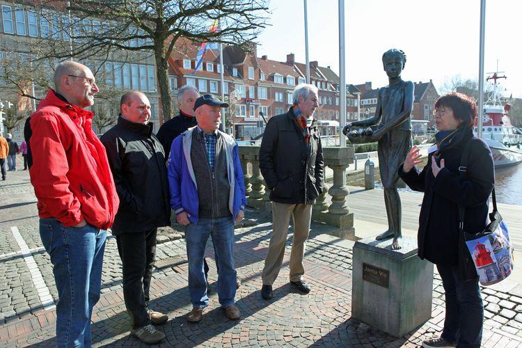 Eine Stadtführerein steht mit einer Gruppe vor der Bronzestatue Janjte Viss und erzählt etwas über die Stadtgeschichte