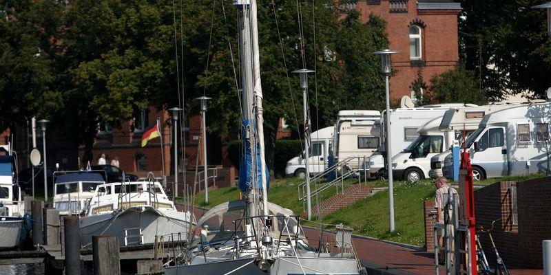 Im Vordergrund Boote im Yachthafen im Hintergrund Wohnmobile in erster Reihe des Wohnmobilstellplatzes