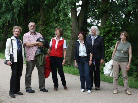 Zu sehen ist eine 6 köpfige Gruppe der Emder Stadtführergilde, auf einem Spazierweg auf dem Emder Wall. Im Hintergrund Bäume und Büsche