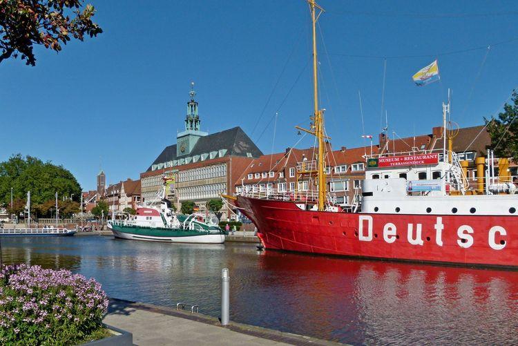 Man sieht den Ratsdelft. Im Vordergrund ein Blumenkasten, auf der gegenüberliegenden Seite das Feuerschiff und der Seenotrettungskreuzer Georg Breusing. Am Kopf des Delftes liegt das Hafenboot. Im Hintergrund ist das ostfriesische Landesmuseum zu sehen.