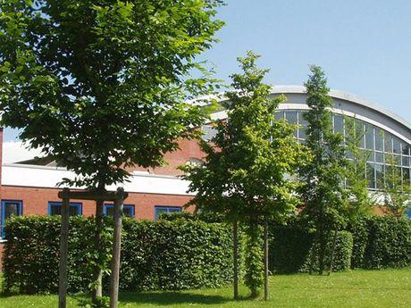 Zu sehen ist die Nordseehalle von außen mit einigen Bäumen im Vordergrund