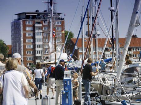 Momentaufnahme von Spaziergängern und Segelbooten am Delft