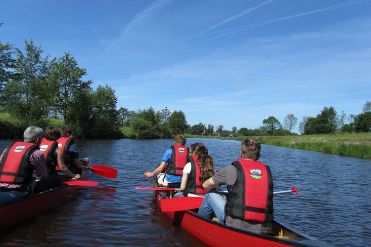 Zu sehen sind zwei Kanu´s mit jeweils 3 Personen in roten Schwimmwesten, auf einem schönen blauem Gewässer