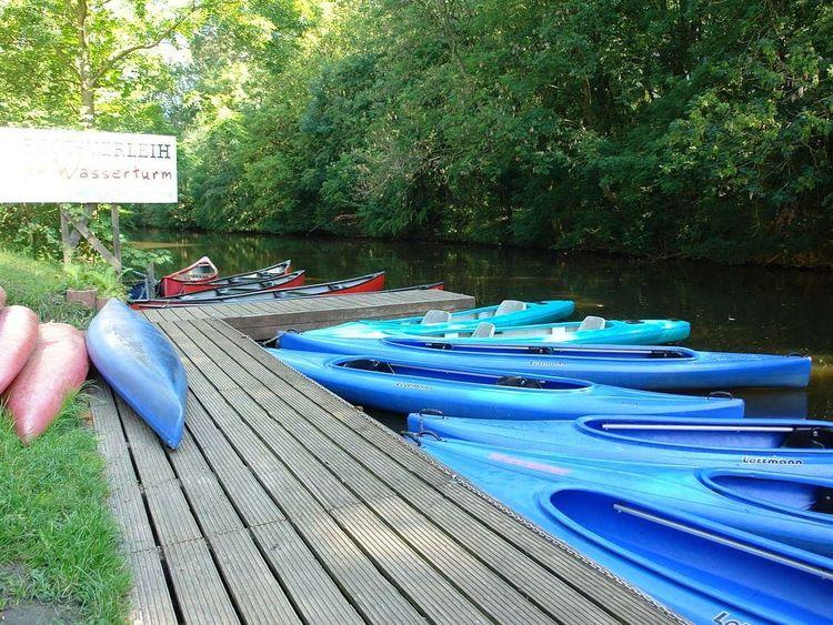 Zu sehen ist der Bootssteg des Bootsverleihes am Wasserturm. Blaue und rote Boote liegen im und neben dem Wasser.