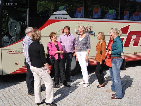 Zu sehen ist eine kleine Reisegruppe, stehend vor einem Reisebus.