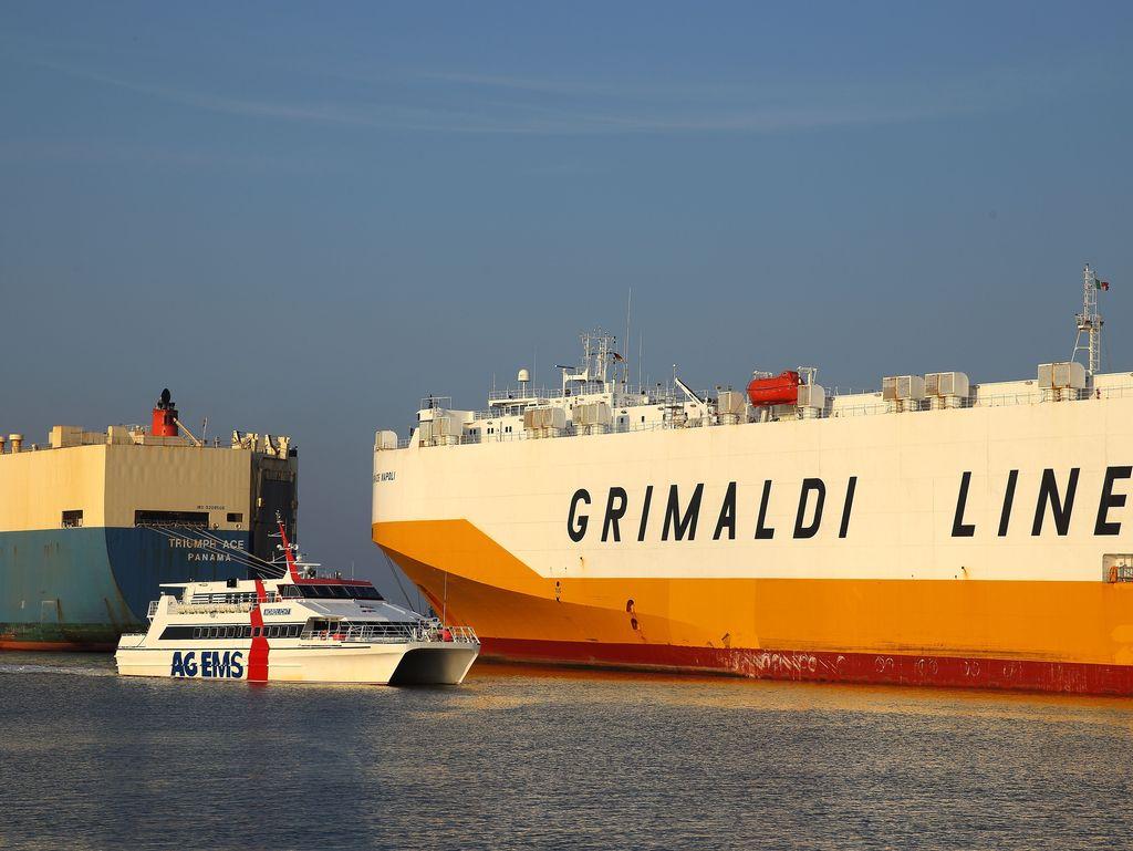 Man sieht den Katamaran der Reederei AG Ems auf seiner Fahrt vorbei an 2 großen Autoverladeschiffen.