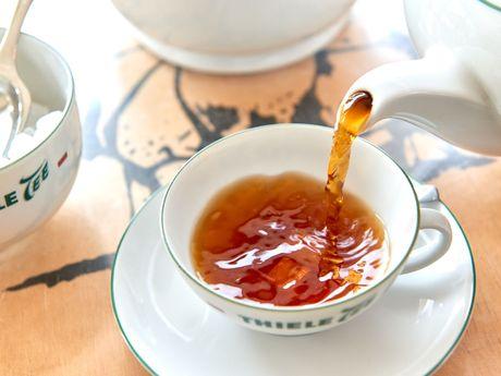 Nahaufnahme wie Bernsteinfarbener Ostfriesen Tee in eine Teetasse gegossen wird