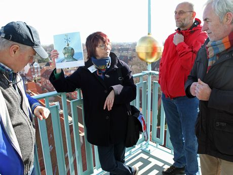 Eine Stadtführerin steht mit einer Gruppe auf dem Rathausturm und erzählt geschichtliches zu Emden
