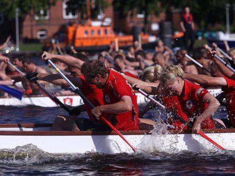 Man sieht ein Teil eines Drachenbootes im Vordergrund und weitere leicht verschwommen im Hitergrund. Das Team kämpft um den Sie und das Wasser spritzt vom Paddeln in alle Richtungen.