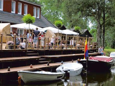 Zu sehen ist der Anleger des Restaurant Bootshaus. Im Vordergrund Boote, dann die Terrasse und das Bootshaus selber.