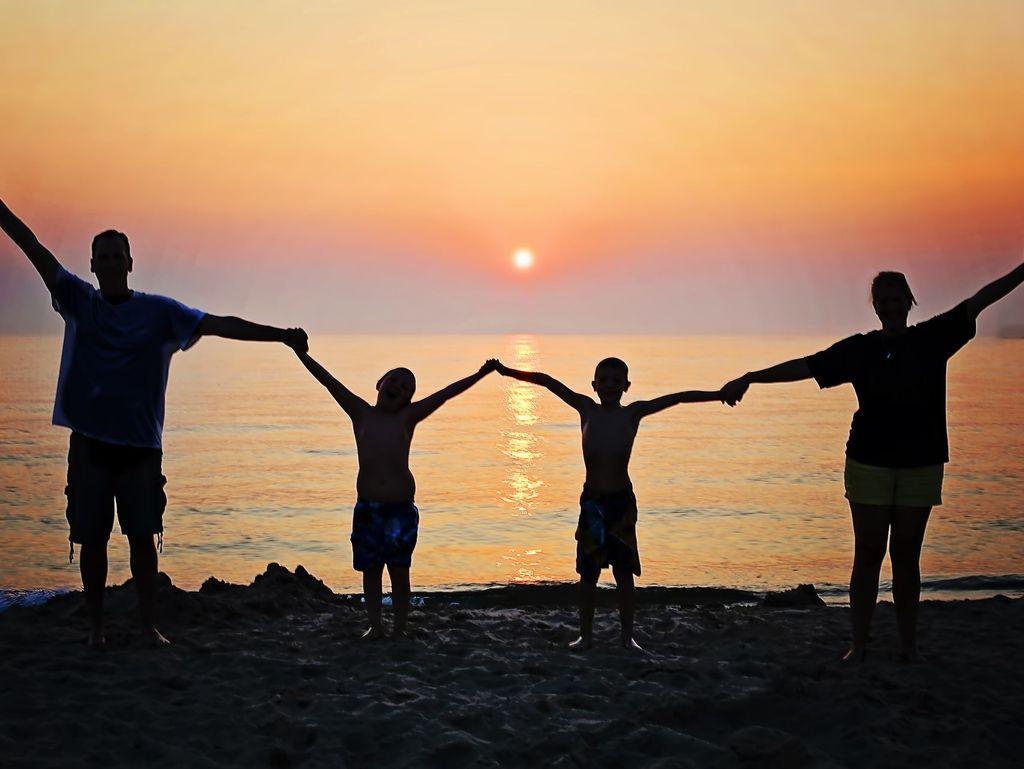Zu sehen ist eine 4-köpfige Familie. Alle halten sich an den Händen und heben die Hände dabei in die Höhe. Sie stehen in einer Reihe und schauen in den Sonnenuntergang. Man erkennt nur dunkle Umrisse der Menschen.
