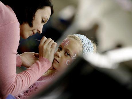Eine Frau schminkt ein kleines Mädchen mit bunten Ornamenten und Blumen im Gesicht.
