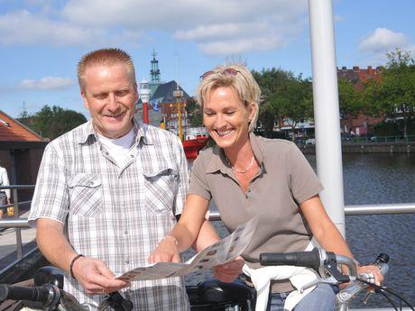 Ein Paar steht mit Fahrrädern auf dem Hafentorplatz und schaut in einen Stadtplan. Im Hintergrund der Ratsdelft, Teile des Feuerschiffes und des Ostfriesischen Landesmuseums