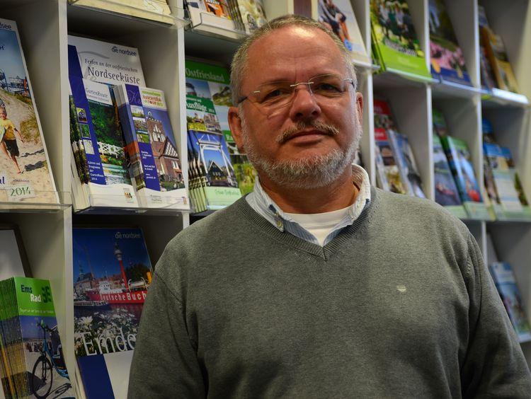 Foto unseres Geschäftsführers Rainer Gerdes vor einer Prospektwand