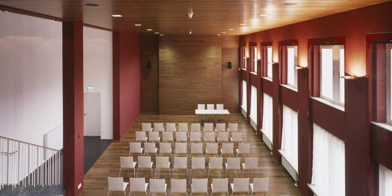 Zu sehen ist ein Raum mit Stuhlreihen, für eine Tagung.