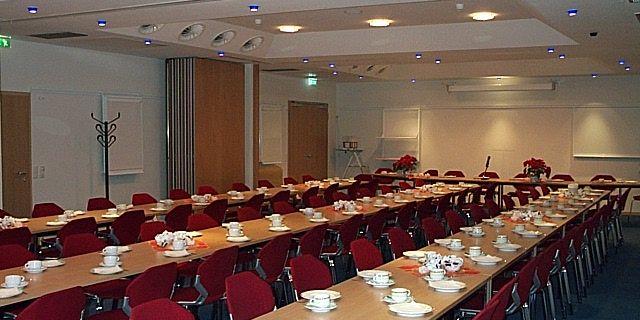 Zu sehen ist ein Tagungsraum der Nordseehalle mit Tischen und Stühlen in Reihen