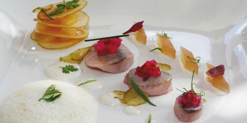 Auf einem weißen Teller sind in der Mitte 3 kleine Matjesfilets mit Rote Beete Tartar oben drauf angerichtet. Darum wurden kleine Gurkenscheiben, Kartoffelscheiben und eine Soße dekoriert.