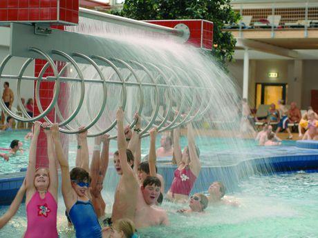 Zu sehen sind Kinder welche unter Duschdüsen im Becken spielen