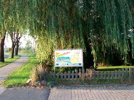 Zu sehen ist ein Stück Straße und die Einfahrt zum Fahrradladen Neef. Ein Werbeschild des Fahrradladens steht am Zaun vor grünen Bäumen