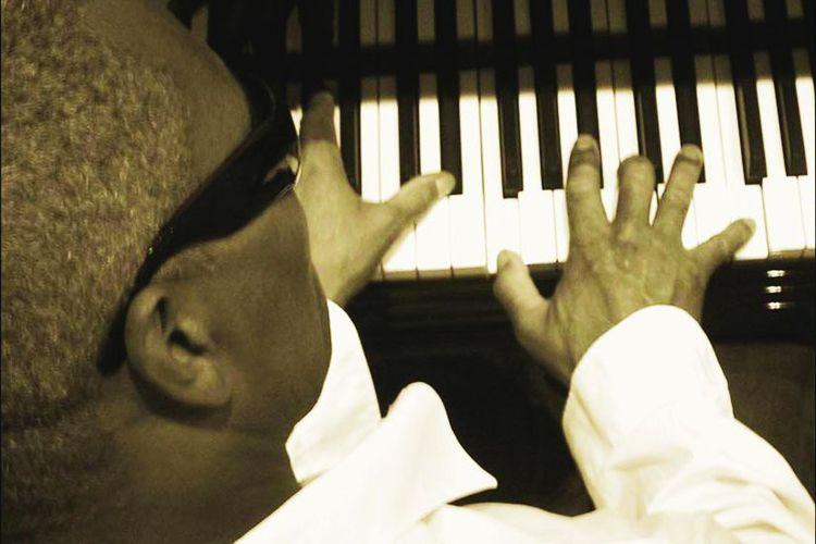 Ein schwarzer Klavierspieler von hinten, oben fotografiert