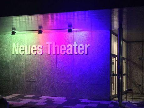 Zu sehen ist eine Außenwand des Neuen Theaters mit dem Schriftzug Neues Theater, welcher in grün, rosa und lila Farbtönen angestrahlt wird.