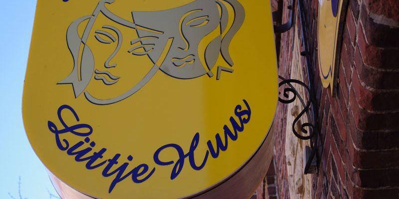 Zu sehen ist das Schild der Friesenbühne Emden. Zwei Theatermasken auf gelben Grund.