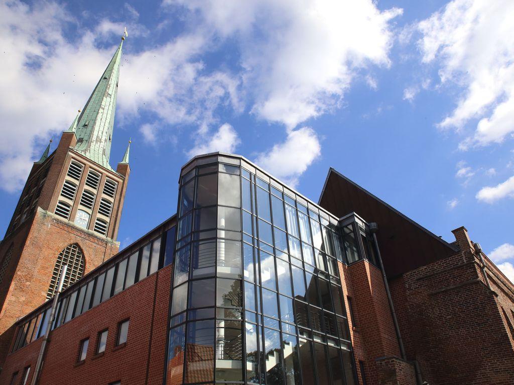 Zu sehen ist der Kirchturm der Johannes a Lasco Bibliothek und der gläserne Teil des neuen Gebäudeteiles.