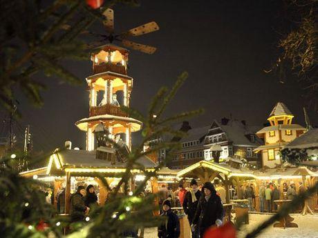 Die beleuchtete Weihnachtspyramide steht im Mittelpunkt des Bildes. Weihnachtsmarktbesucher schlendern durch das Bild