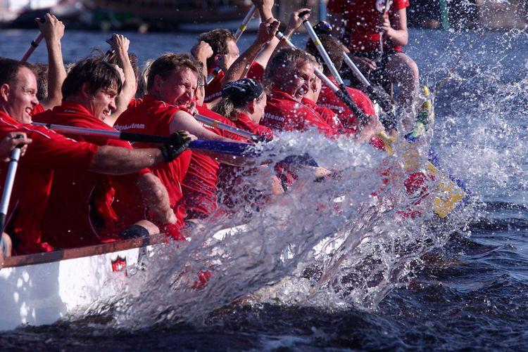 Nahaufnahme eines Drachenbootes. Man sieht wie das Team paddelt und um den Sieg kämpft. Das Wasser spritzt von der Paddelbewegung in alle Richtungen.