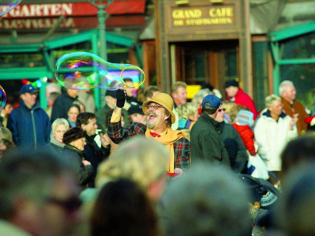 Verkleideter Seifenblasenkünstler macht eine riesen Seifenblase inmitten einer zuschauenden Menschenmenge