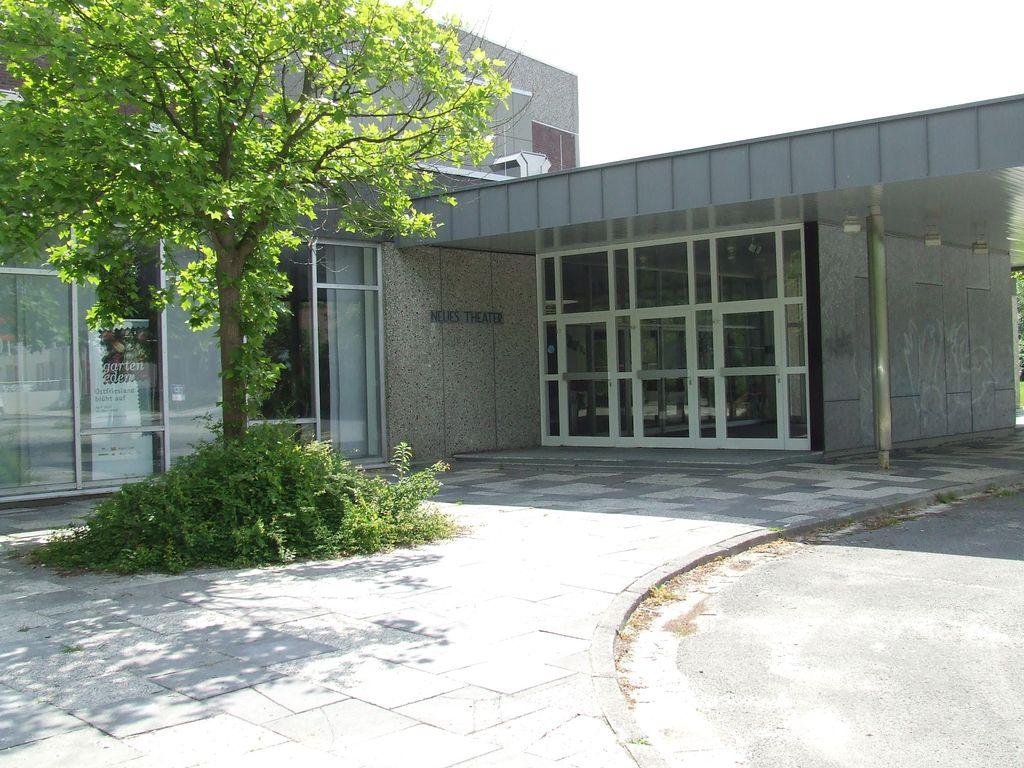 Zu sehen ist der Außenbereich des Neuen Theaters, im Vordergrund ein Baum