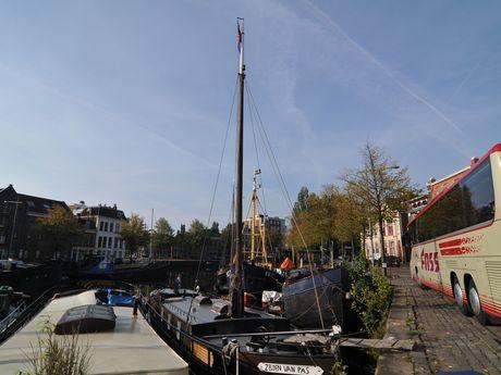 Zu sehen sind Boote in einem Kanal und daneben ein Reisebus.