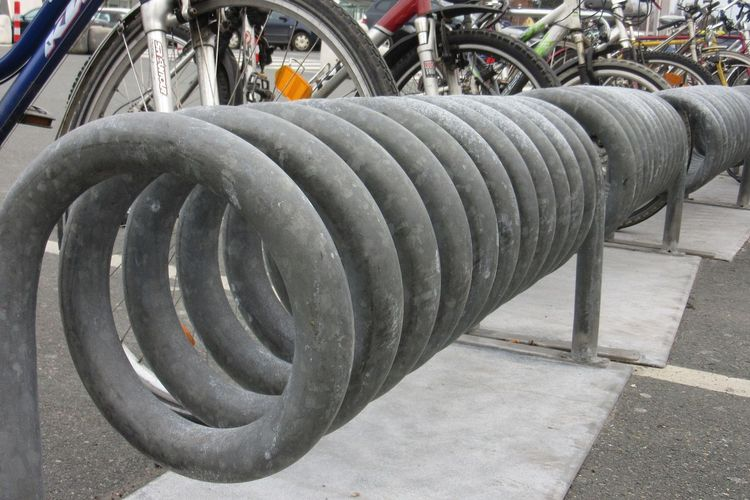 Zu sehen ist ein spiralförmiger Fahrradständer im Vordergrund und Teile abgestellter Fahrräder