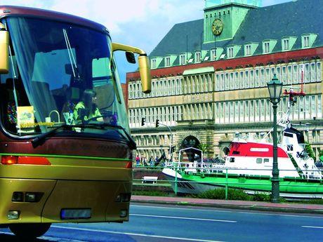 Die Front eines Reisebusses seitlich im Bild. Im Hintergrund der Seenotrettungskreuzer Georg Breusing und das Ostfriesische Landesmuseum