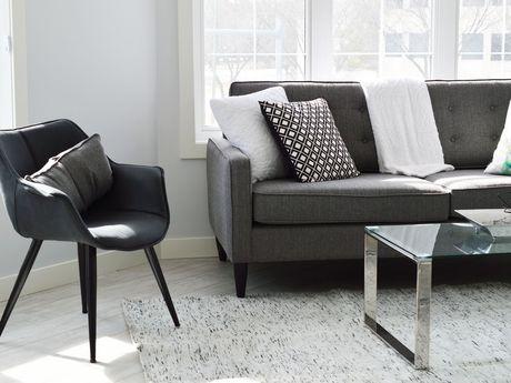 Zu sehen ist eine Couch in grau, ein Stuhl und ein Tisch.